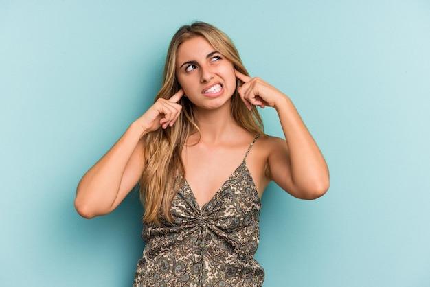 Jovem mulher loira caucasiana isolada em um fundo azul, cobrindo as orelhas com os dedos, estressada e desesperada por um ambiente barulhento.