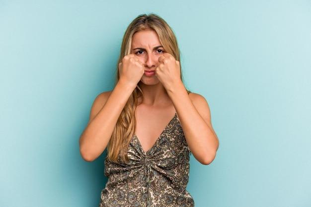 Jovem mulher loira caucasiana isolada em um fundo azul, dando um soco, raiva, lutando devido a uma discussão, boxe.