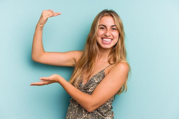 Jovem mulher loira caucasiana isolada em um fundo azul, segurando algo pequeno com os indicadores, sorrindo e confiante.