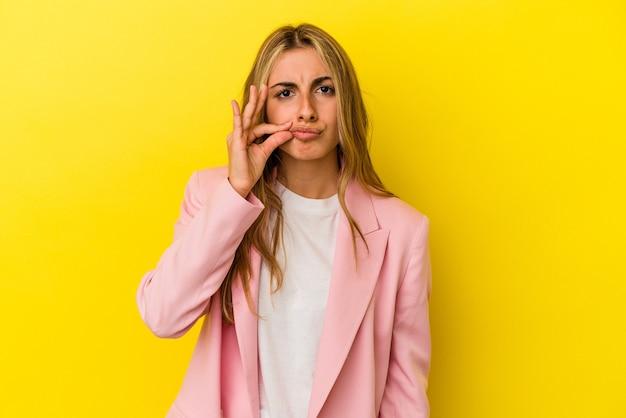 Jovem mulher loira caucasiana isolada na parede amarela com os dedos nos lábios, mantendo um segredo.