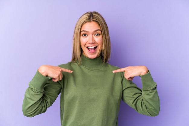 Jovem mulher loira caucasiana isolada surpresa apontando com o dedo, sorrindo amplamente.