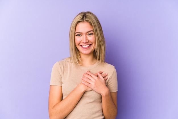 Jovem mulher loira caucasiana isolada tem uma expressão amigável, pressionando a palma da mão no peito. conceito de amor.