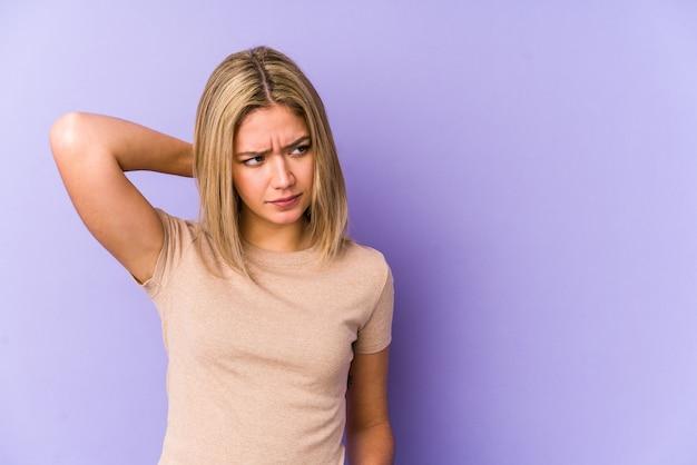 Jovem mulher loira caucasiana isolada tocando a parte de trás da cabeça, pensando e fazendo uma escolha.
