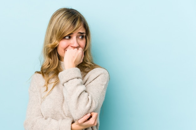 Jovem mulher loira caucasiana roendo as unhas, nervosa e muito ansiosa.