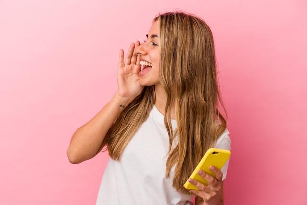 Jovem mulher loira caucasiana segurando um celular amarelo isolado gritando e segurando a palma da mão perto da boca aberta.