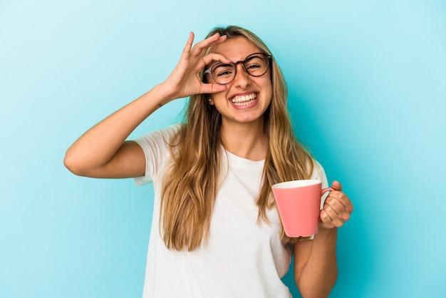 Jovem mulher loira caucasiana, segurando uma caneca isolada sobre fundo azul, animada em manter o gesto ok no olho.