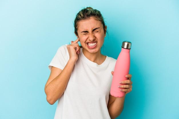 Jovem mulher loira caucasiana segurando uma garrafa térmica isolada em um fundo azul, cobrindo as orelhas com as mãos.
