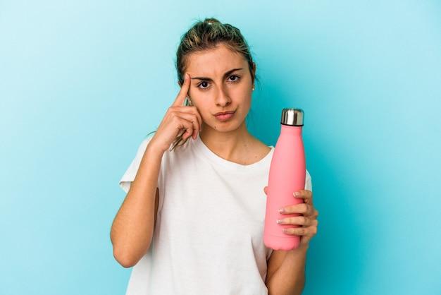 Jovem mulher loira caucasiana segurando uma garrafa térmica isolada no fundo azul, apontando o templo com o dedo, pensando, focada em uma tarefa.