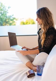 Jovem mulher loira caucasiana sentada em sua cama em casa com um laptop assistindo canais da série em streaming Foto Premium