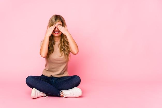 Jovem mulher loira caucasiana sentada em um estúdio rosa cobre os olhos com as mãos, sorri amplamente esperando por uma surpresa.