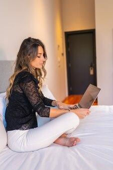 Jovem mulher loira caucasiana sentada na cama em casa assistindo noticiários online e redes sociais