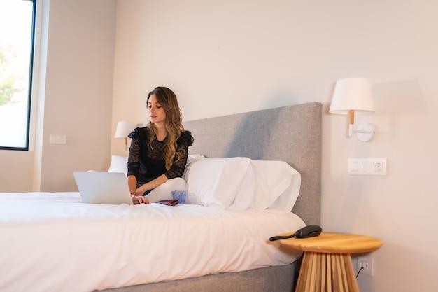 Jovem mulher loira caucasiana sentada na cama em casa com um laptop assistindo a notícias online e redes sociais