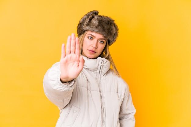 Jovem mulher loira caucasiana vestindo uma roupa de inverno isolada em pé com a mão estendida, mostrando o sinal de stop, impedindo você.
