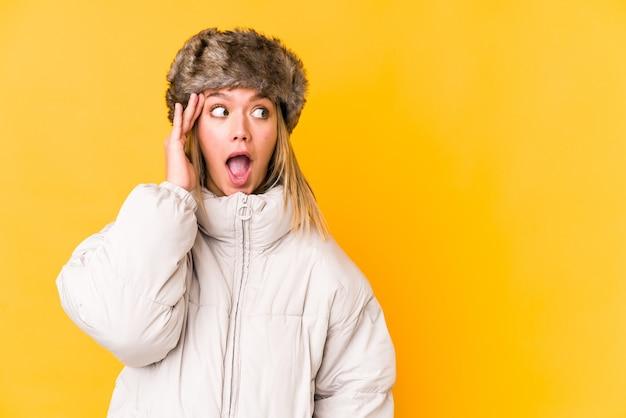 Jovem mulher loira caucasiana, vestindo uma roupa de inverno isolada grita alto, mantém os olhos abertos e as mãos tensas.