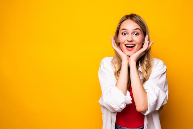 Jovem mulher loira chocada e animada posando isolada na parede amarela