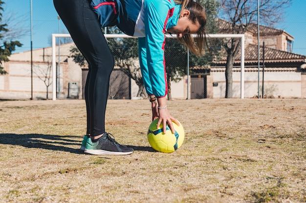 Jovem mulher loira colocando futebol amarelo em posição de lance livre. campo de futebol de campo.