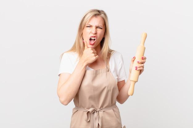 Jovem mulher loira com a boca e os olhos bem abertos e a mão no queixo. conceito de padeiro