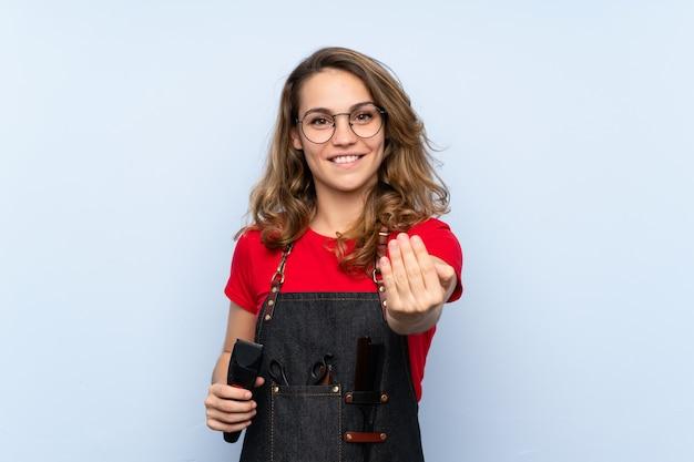 Jovem mulher loira com avental de cabeleireiro e segurando a máquina de corte de cabelo