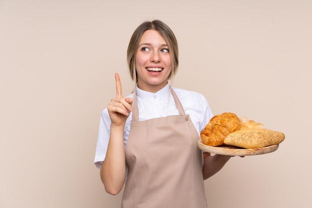 Jovem mulher loira com avental. padeiro feminino segurando uma mesa com vários pães com a intenção de realizar a solução enquanto levanta um dedo