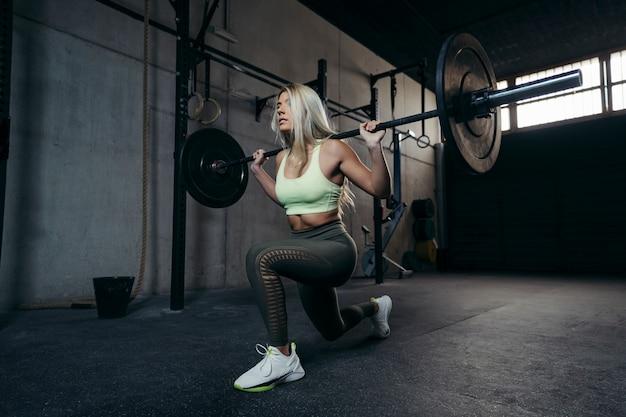 Jovem mulher loira com barra, fazendo um treino de perna.