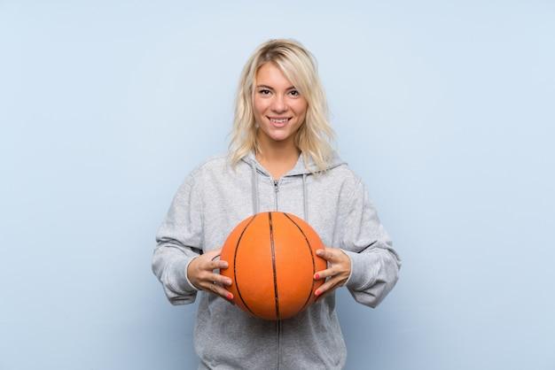 Jovem mulher loira com bola de basquete