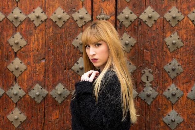 Jovem mulher loira com cabelo comprido, posando em uma porta de madeira antiga.