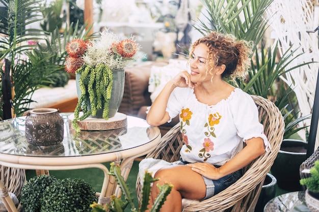 Jovem mulher loira com cabelo encaracolado, sentada em uma cadeira de vime com muitas plantas, admira a vegetação. conceito de relaxamento e lazer. cores verdes e pessoas