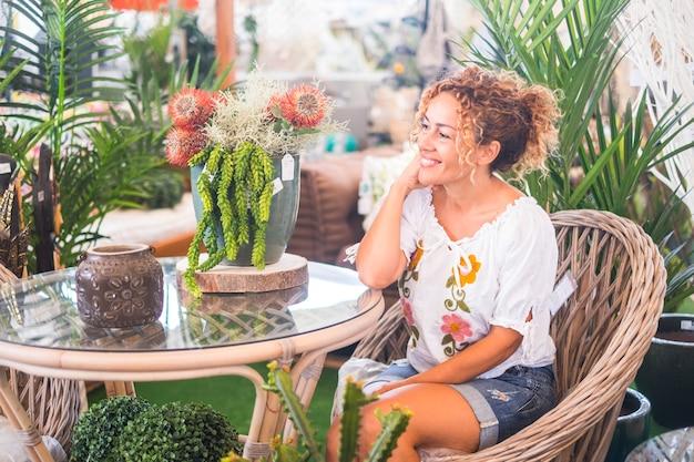 Jovem mulher loira com cabelo encaracolado, sentada em uma cadeira de vime com muitas plantas, admira a vegetação. conceito de relaxamento e lazer para quem gosta da natureza e do meio ambiente