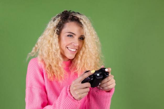 Jovem mulher loira com cabelo longo encaracolado em um suéter rosa verde com joystick jogando