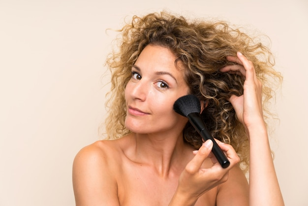 Jovem mulher loira com cabelos cacheados com pincel de maquiagem