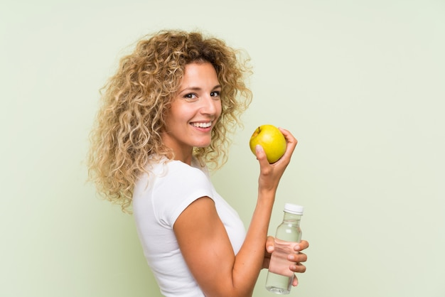 Jovem mulher loira com cabelos cacheados com uma maçã e uma garrafa de água