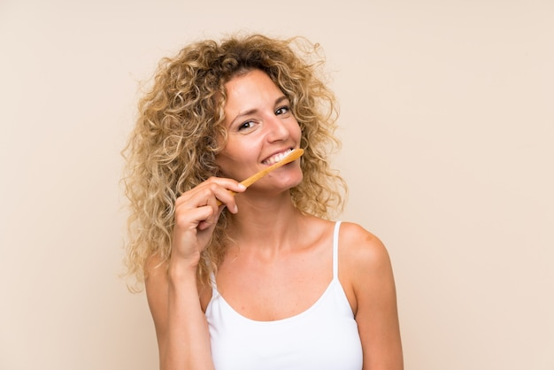 Jovem mulher loira com cabelos cacheados, escovando os dentes