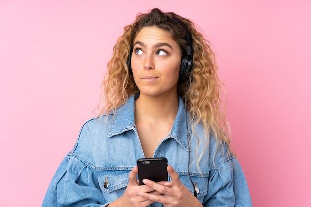 Jovem mulher loira com cabelos cacheados na parede rosa, ouvindo música com um celular e pensando