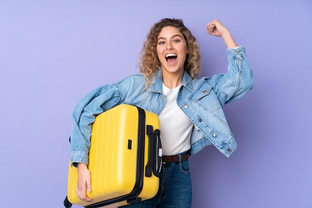 Jovem mulher loira com cabelos cacheados na parede roxa em férias com mala de viagem
