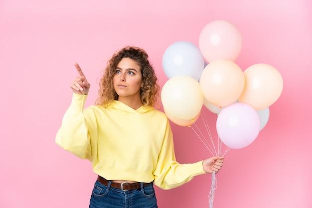 Jovem mulher loira com cabelos cacheados, pegando muitos balões na parede rosa tocando na tela transparente