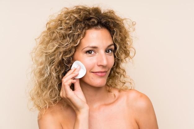 Jovem mulher loira com cabelos cacheados, remover a maquiagem do rosto com almofada de algodão