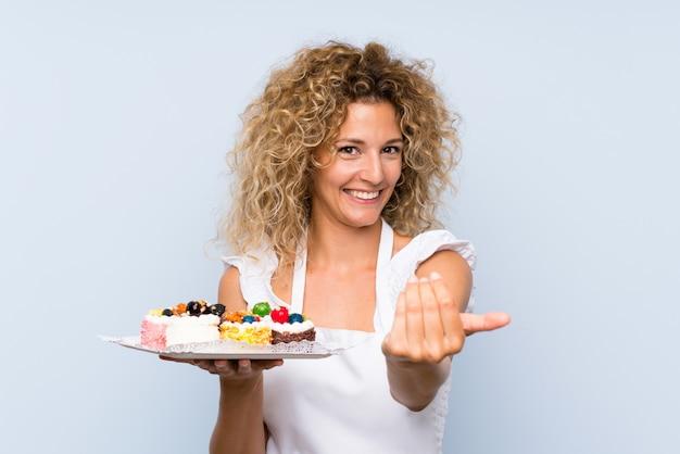 Jovem mulher loira com cabelos cacheados, segurando muitos mini bolos diferentes, convidando para vir com a mão. feliz que você veio
