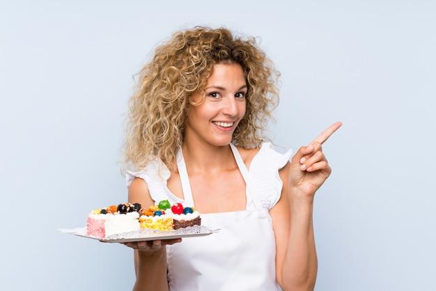 Jovem mulher loira com cabelos cacheados, segurando muitos mini bolos diferentes, surpreendendo e apontando o dedo para o lado