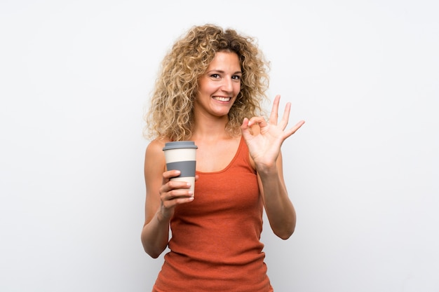 Jovem mulher loira com cabelos cacheados, segurando um café longe mostrando sinal ok com os dedos