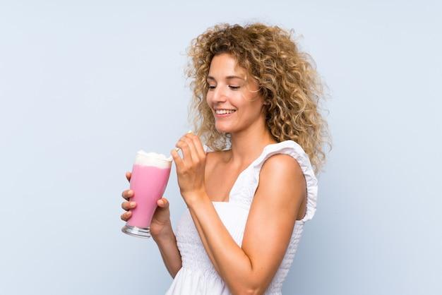 Jovem mulher loira com cabelos cacheados, segurando um milk-shake de morango