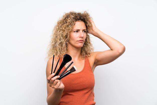 Jovem mulher loira com cabelos cacheados, segurando um monte de pincel de maquiagem com dúvidas e com a expressão do rosto confuso