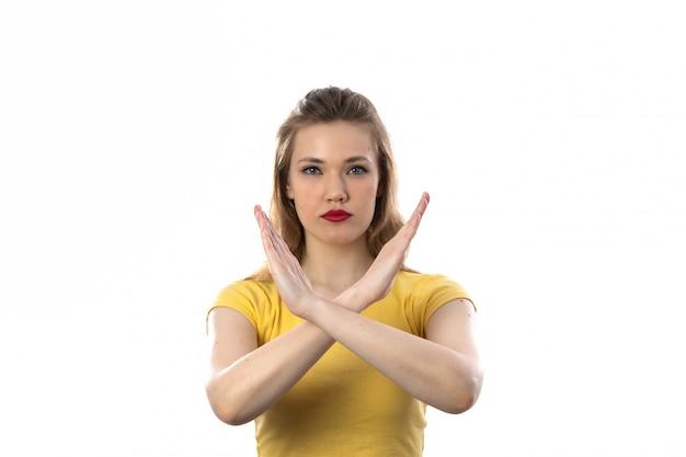 Jovem mulher loira com camiseta amarela diz não com os braços