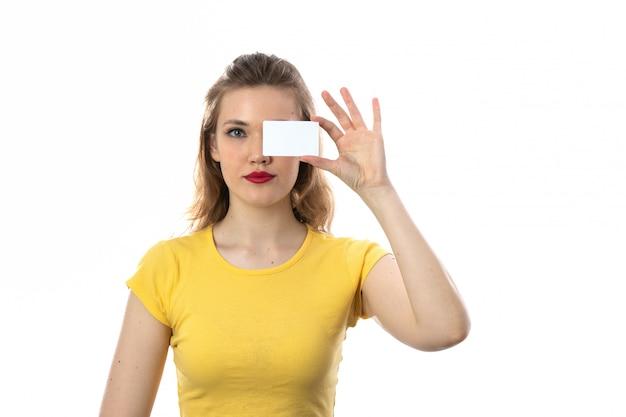 Jovem mulher loira com camiseta amarela segurando o cartão de visita em branco