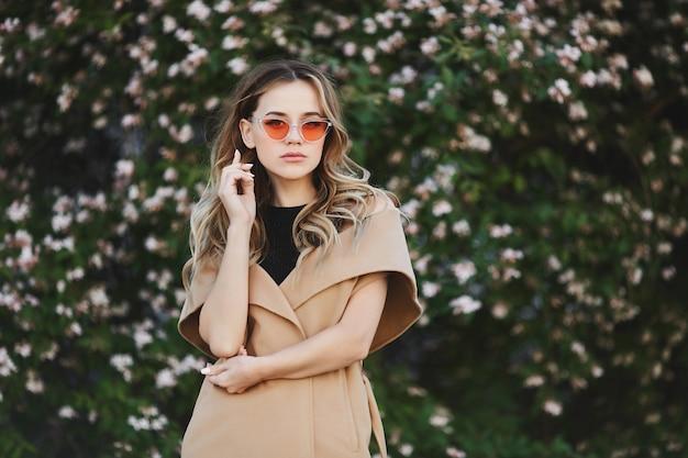 Jovem mulher loira com casaco sem mangas e elegantes óculos de sol posando ao ar livre perto de árvore florescendo.