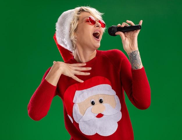 Jovem mulher loira com chapéu de natal e suéter de natal de papai noel com óculos segurando o microfone perto da boca tocando o peito cantando com os olhos fechados isolado no fundo verde