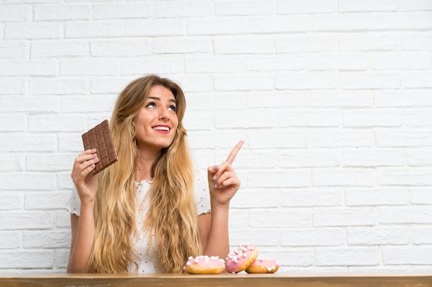 Jovem mulher loira com chocolat apontando para cima