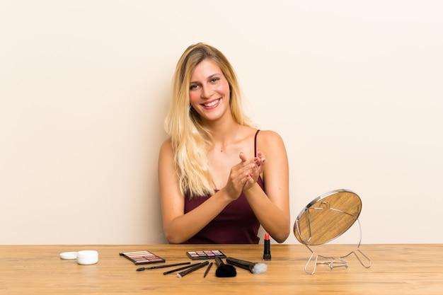 Jovem mulher loira com cosméticos em uma mesa aplaudindo