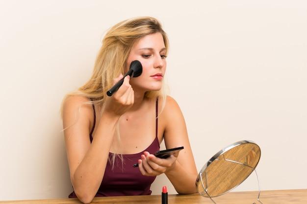 Jovem mulher loira com cosméticos em uma tabela