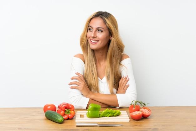 Jovem mulher loira com legumes em uma mesa rindo