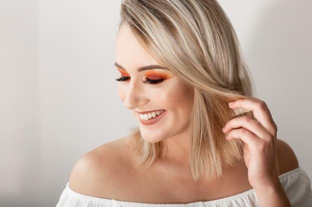 Jovem mulher loira com maquiagem brilhante